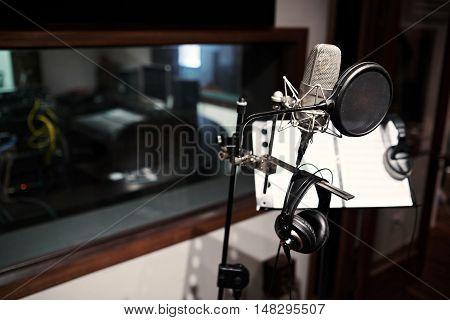 Modern microphone in recording studio, selective focus