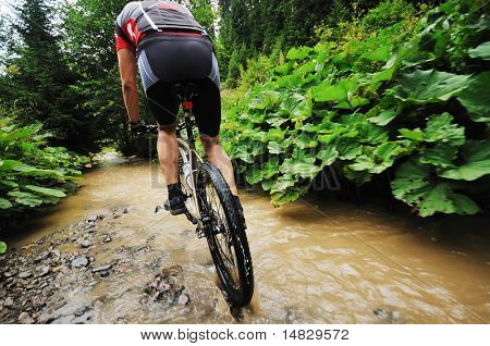 young man drive mountain bike over water river