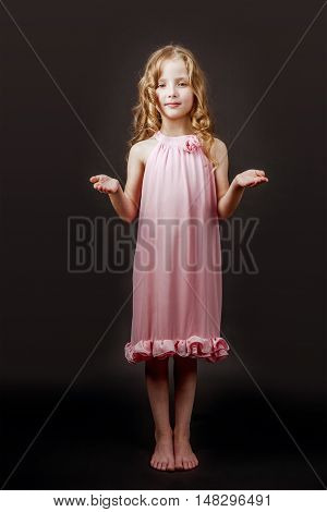 Charming little girl stands barefoot in pink dress on the black wall backdrop