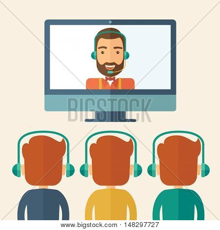 A happy Caucasian businessman in a monitor with beard giving a business presentation with three men infront of him wearing their headphones to hear the voice of the presentor. Business presentation