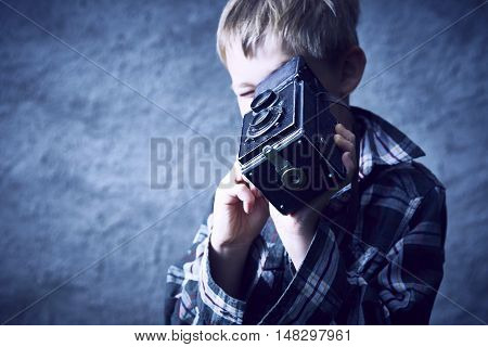 Child blond boy with vintage photo film camera photographing outside