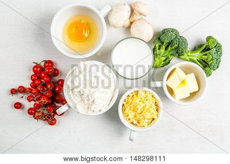 The selection of ingredients for the preparation of traditional French dishes quiche lorraine, on white wooden table, top view, copy space