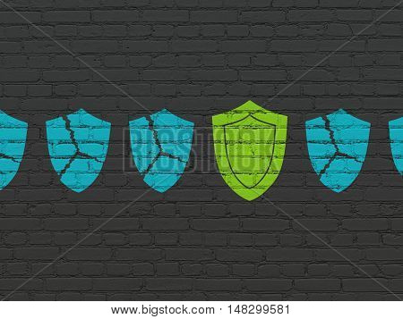Protection concept: row of Painted blue broken shield icons around green shield icon on Black Brick wall background