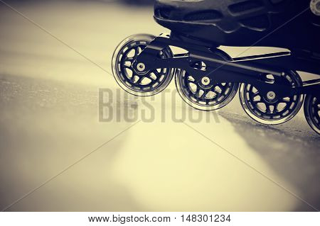 Background with the road and wheels of roller skates closeup