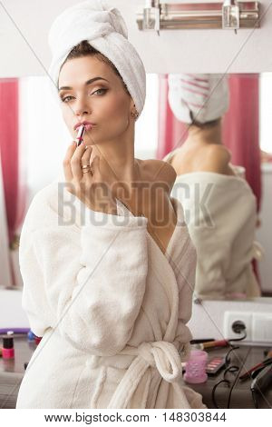Young beatiful woman doing makeup, sitting at dressing table at home.