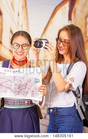 Two beautiful young women posing, one wearing traditional andean clothing, the other in casual clothes with camera, holding city map interacting, both smiling, park background.