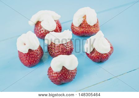 Fresh strawberries and whipped cream on wooden background