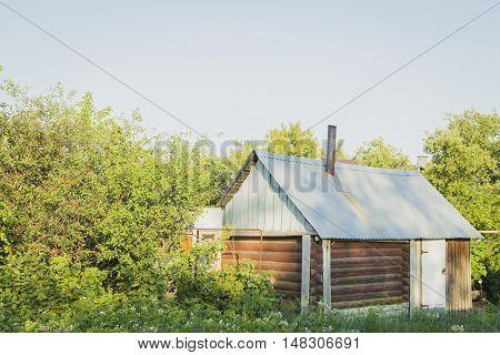 Village landscape - old bathhouse, smoke raising from a chimney