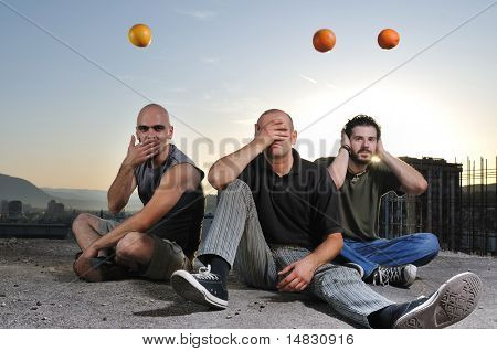 group of three young man outdoor in urban scene playing and have fun with orange fruit at sunset