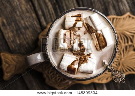 Cup of hot cocoa with marshmallow on cutting board wooden table background