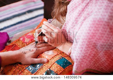 young woman mehendi artist painting henna on the hand for man.