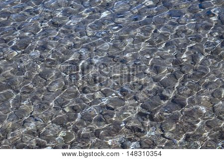 Shallow sea with pebble stones as a background