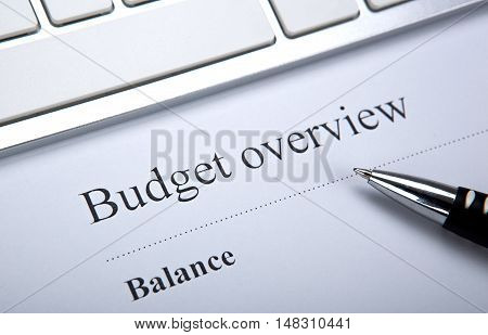document with title budget overview and keyboard close up