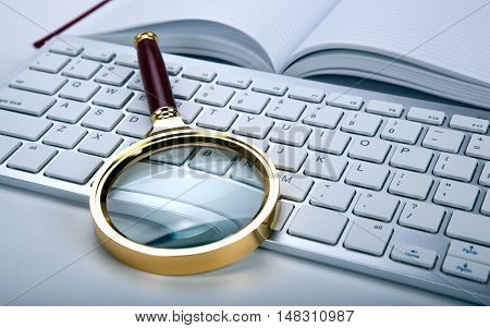 magnifier and computer keyboard on the desktop close up