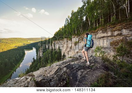 Young woman hiker with backpack standing on cliff and looking far away enjoying beautiful view.