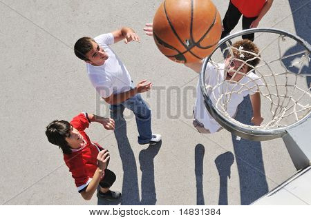 group of young boys who playing basketball outdoor on street with long shadows and bird view perspective