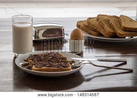 Six pieces of sliced wheat bread covered with chocolate beside milk and egg in holder. Dutch Breakfast meal.