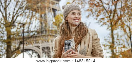 Tourist Woman Near Eiffel Tower With Cellphone Looking Aside