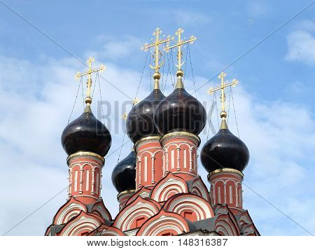 Top of Russian Christian church colored pink with cupolas with golden crosses over blue sky with white clouds closeup