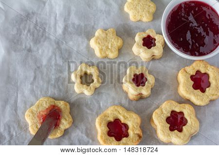 Flower Shaped Sugar Cookies with Jam Filling from Above on Baking Paper Horizontal with Copy Space