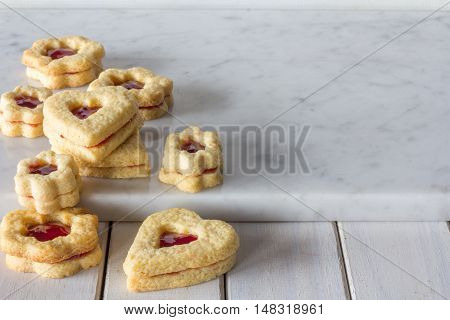 Homemade Jam Filled Sugar Cookies Stacked on Marble Board Horizontal with Copy Space