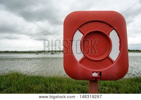 Single red and white emergency rescue lifebuoy standing on the side of a river.
