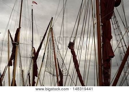 Many yacht masts and rigging set against an overcast stormy sky