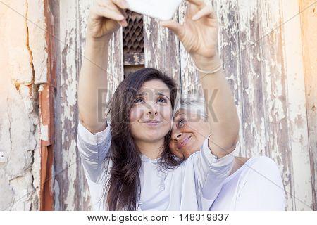 Mother And Adult Daughter Take A Selfie Outdoors