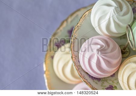 Pastel Meringues from Above on Vintage Tiered Plate with Copy Space