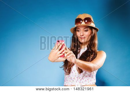 Technology and internet. Happy woman using cellphone texting on mobile phone. Teen girl reading sms on smartphone taking selfie on blue