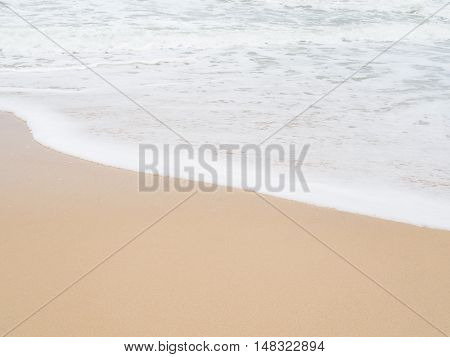 Beach. Soft white wave foam of the sea on sandy beach at Phuket Thailand. Summer time at sea beach concept. Copy space for some text.