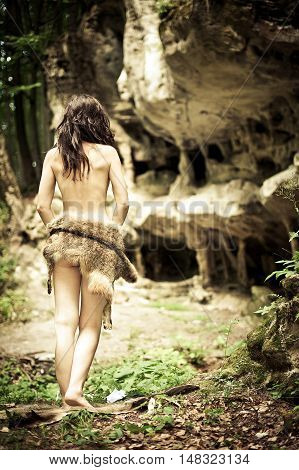 Beautiful young brunette woman wearing a wolf skin in the green forest near the ancient caves