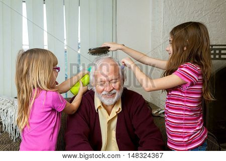 Two young girls style the hair of their grandfather as he sits and laughs. They are brushing putting in ponytails and spraying it.