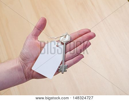 a white paper tag attached to the metal silver key in hand