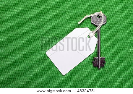 white paper tag attached to the metal silver key on the green background