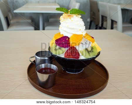 Bingsu fruits berry. Bingsu is local Korean shaved ice dessert serve with toppings such as chopped fruit mango orange kiwi strawberry dragon fruit and berry syrup.