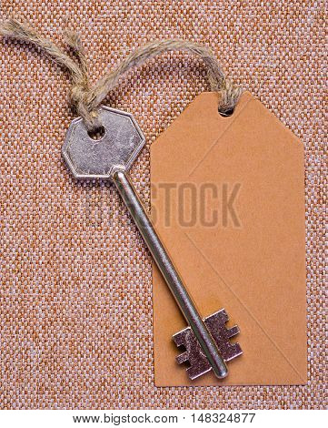brown paper tag attached to the metal silver key on the brown background