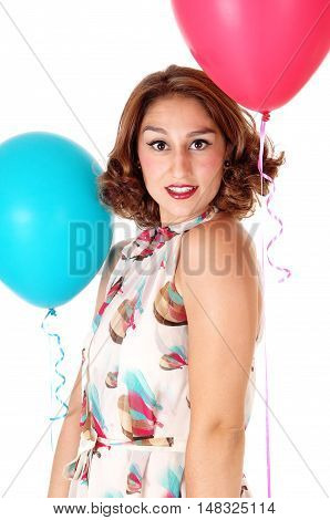 A very pretty young woman standing in a summer dress and holding two balloons isolated for white background.