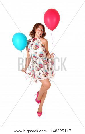 A beautiful woman in a summer dress holding balloons and dancing isolated for white background.