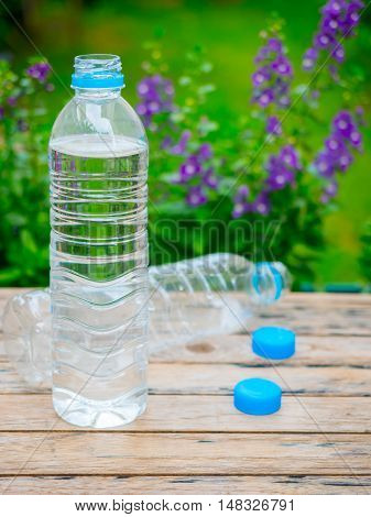 Water Bottle on wood table with garden scene background