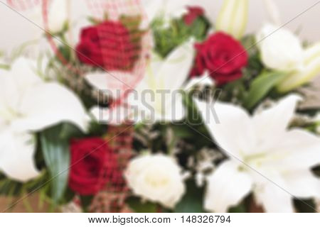 Colorful flowers (bouquet) blurred background. Unfocused bouquet of white lilies and red roses. Floral background