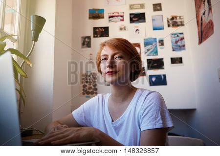 One Modern Female Coworker Smiling During Working Process.Young Hipster Working Startup Project.Woman short hair and white tshirt typing computer morning light. Productive job concept comfy place