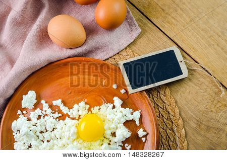 curdson a clay plate,   two eggs and a blank tag,  on wooden background