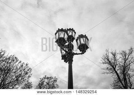 Historic shape black lamppost with four lanterns in front of sky and clouds background .
