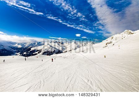 Ski resort in the Alps. Panoramic view of the mountains. People skiing and snowboarding. Mayerhofen, Austria