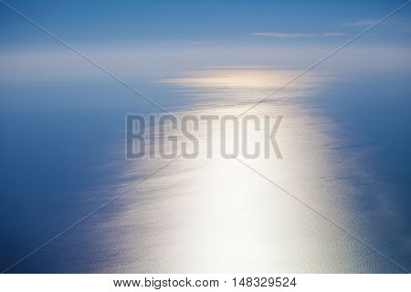 Water sea surface on the sunset, aerial view from the plane porthole