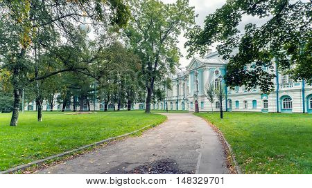 Smolny Garden Park in Saint Petersburg, Russia. Walkway with Green Trees. Beautiful Alley at Autumn Time.