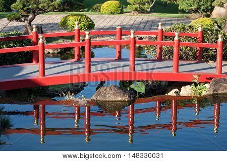 Chinese garden bridge reflex on lake water