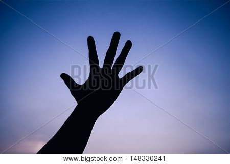 Silhouette of a hand on colorful sky background. Symbol is mean to say hi five hand up stop. Outdoors. Outdoor. Cool colors tone photo effect.