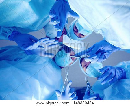 Surgeons holding medical instruments in hands and looking at patient